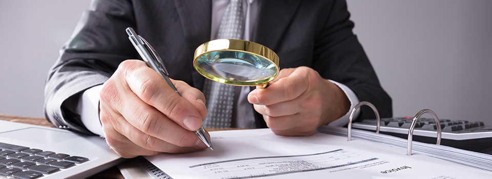 business man investigating paperwork with magnifying glass